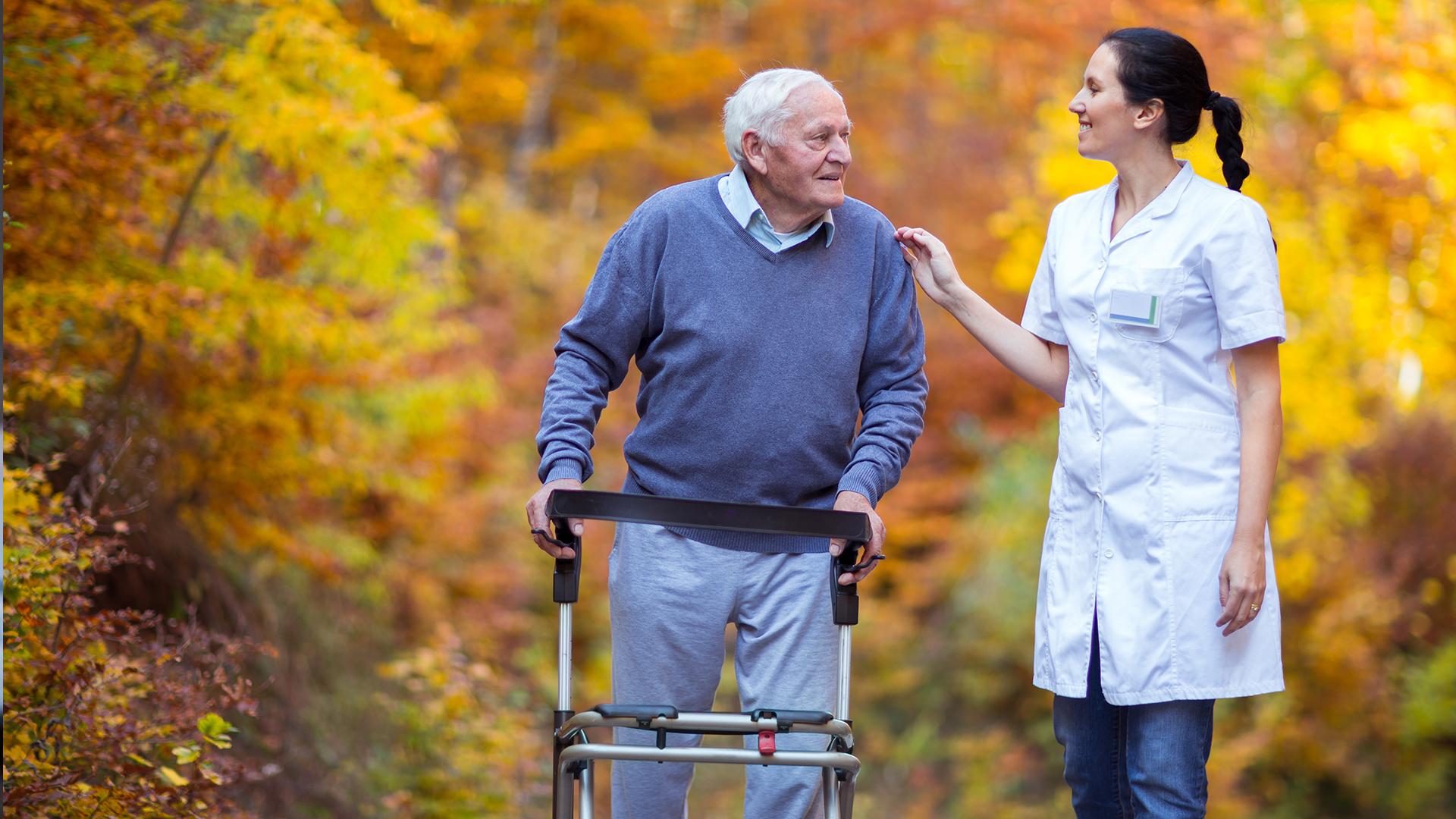 Hombre mayor paseando con una enfermera en un bosque